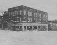 This 1930s winter scene of the Fronefield Building in Wayne, Pa., shows two directional keystone markers. This is Wayne's most prominent intersection, and the signs point to nearby towns: on the left sign (pointing east and west): Philadelphia, Coatesville, Lancaster, and Pittsburgh. On the right sign (pointing north and south): Newtown Square and Media (two more are illegible). (Radnor Historical Society)