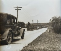 "An automobile approaches a ""Warning: Curve to Left"" marker. (Pennsylvania Department of Highways Collection, Pennsylvania State Archives: RG-12 OL 5-0607 carton 5, #2574)"